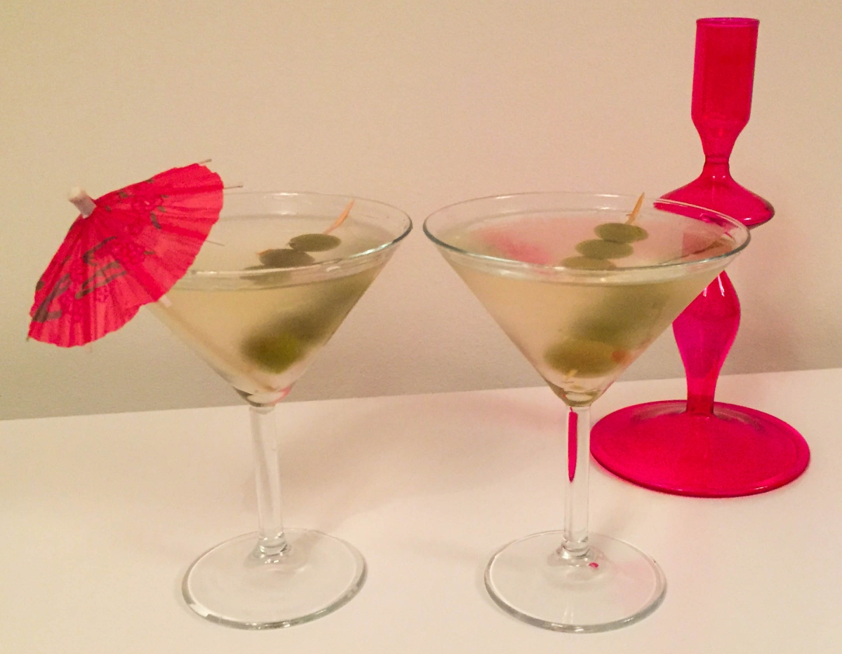 A photograph of two Martini cocktails. One with a cocktail umbrella in the glass.