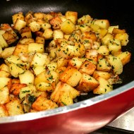 A photograph of sautéed potatoes in a large red frying pan.