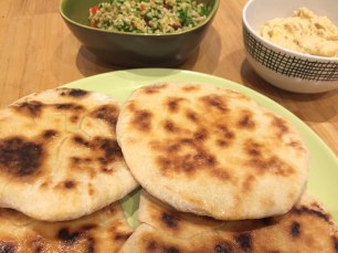 A close up of the cooked flatbreads served on a green plate