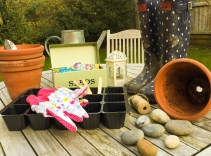 A photograph of various gardening items, laid out on a wooden patio table.