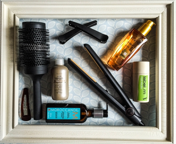 A photograph of hair care products and accessories, composed in a wooden picture frame.