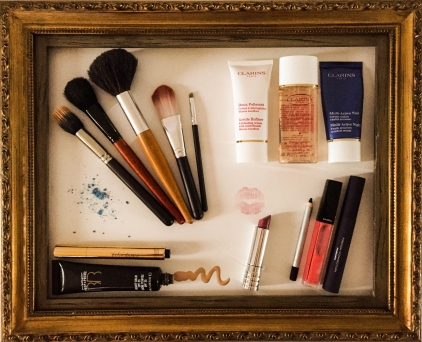 A photograph of makeup and cosmetics composed in a wooden picture frame.
