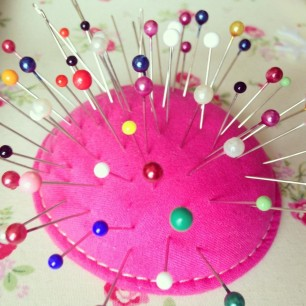Photo of a pin cushion with colourful pins and needles pushed into it
