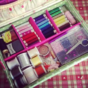 Photo of the inside of a sewing box with thread and sewing accessories