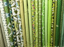 A photograph of different green textile rolls stacked vertically in a haberdashery shop.