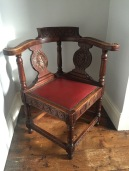 A photo of a beautiful antique corner chair with red leather seat