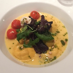 A photo of crab ravioli in a white wine sauce served on a white plate