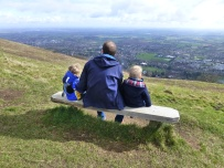 A photo of Rob and the boys sitting on a bench looking down towards Great Malvern and Worcester.
