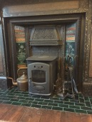 A photo of a Victorian fireplace with working wood burning stove and copper kettle