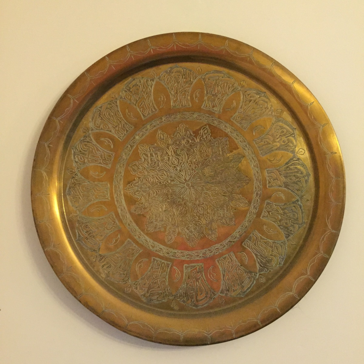 A photo of a beautiful wall mounted dish or plate, possibly brass