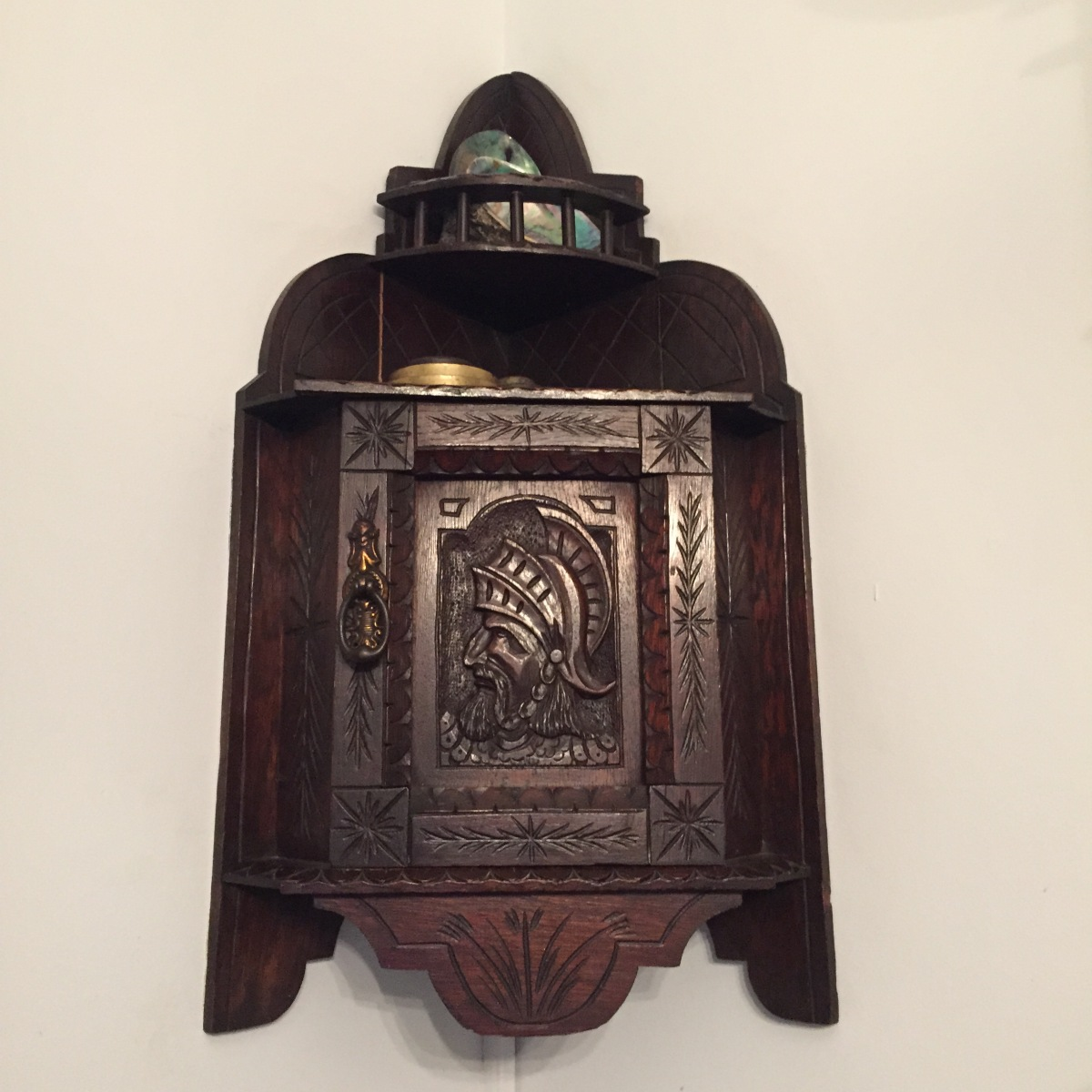 A photo of a dark wooden corner box with intricate carving