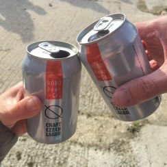 A close up of two cans of Hobo Beer + Co. lagers. Rob and Emma are saying Cheers!