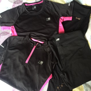 Photograph of some new training clothes bought by Emma. Black tops and black trousers, all with pink trim
