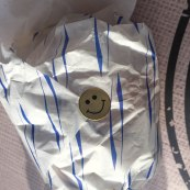 A photo of a smiley face sticker on the burger packaging from GoGo Gogi Gui.