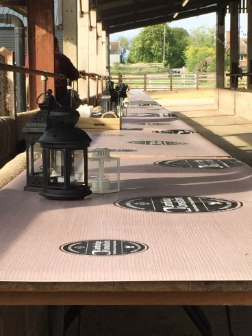 A photo of a line of trestle tables with napkins, cutlery and candles.