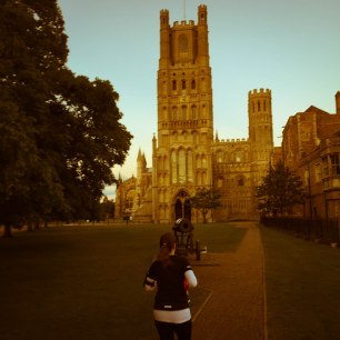 A photo of Emma running around Palace Green, opposite Ely Cathedral.