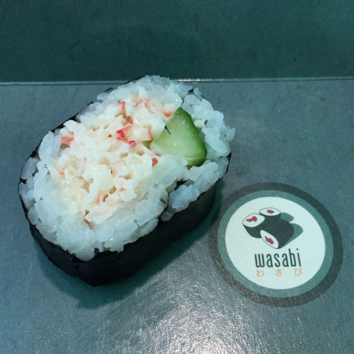 A close up photograph of a crabmeat and cucumber roll.