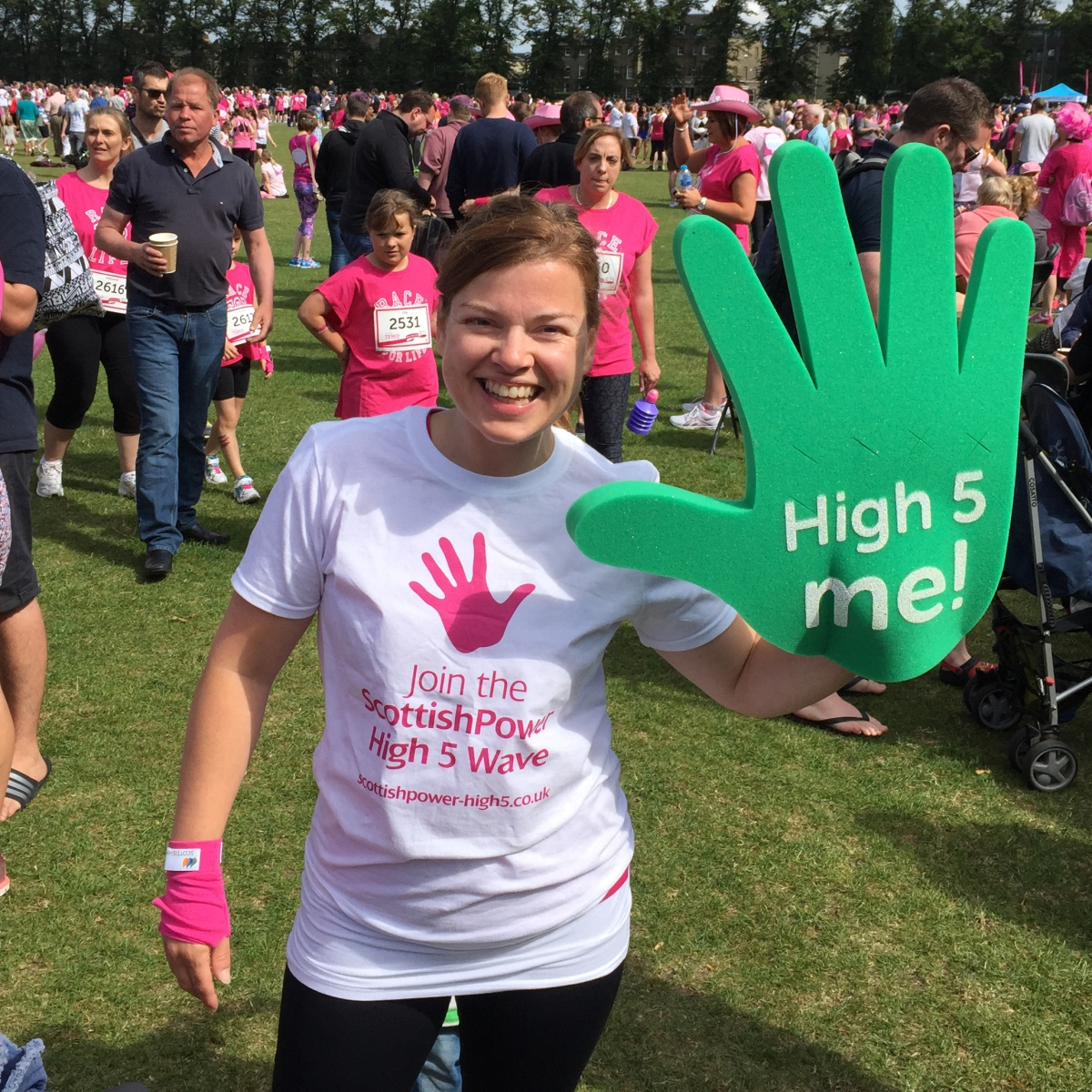 "A photograph of Emma holding the giant green hand from the Scottish Power ""High 5 Wave"" campaign."