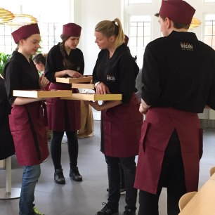 A photograph of some of the Wasabi staff in burgundy and black uniform.