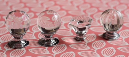 A photograph of the four transparent drawer knobs displayed on pink leaf paper