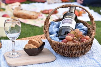 A photograph of a vintage grape basket with grapes and a bottle of wine