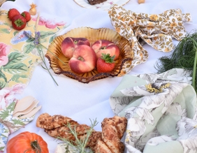 A photograph of three peaches and some beautiful floral napkins and scarves to add interest