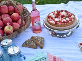 A photograph of some apples, pink lemonade and a strawberry tart