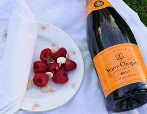 A close up of a bottle of Veuve Clicquot and a plate of raspberries and nuts