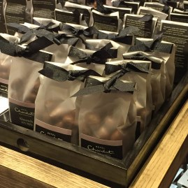 A photograph of small bags of milk chocolate salted caramelised almonds