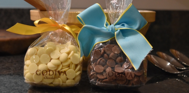 A photograph of some Godiva white and milk chocolate buttons in separate bags with yellow and blue ribbons