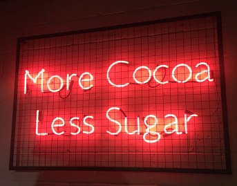 A photograph of a neon red sign saying More Cocoa Less Sugar