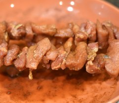 A photograph of the pork on skewers in the aromatic marinade