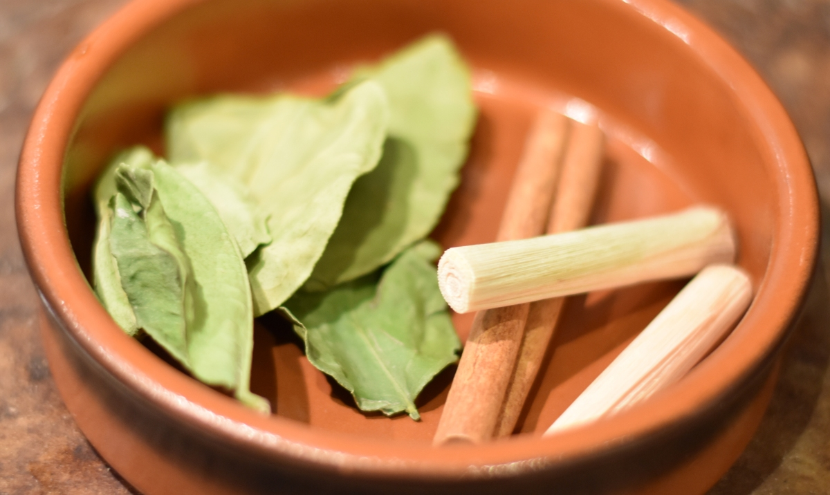 A photograph of the whole spices in a shallow brown dish: Kaffir lime leaves, cinammon stick and lemongrass stalks