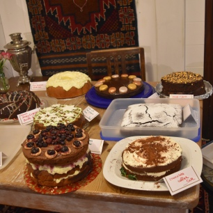 A photograph of all the Ely Clandestine Cake Club cakes all laid out on a table at the Samovar.