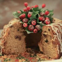 A close up photograph of Emma's Festive Bundt cake with fake holly and berries on the top and about a third sliced away and eaten.