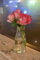 A photograph of three pink roses in a clear glass bottle.