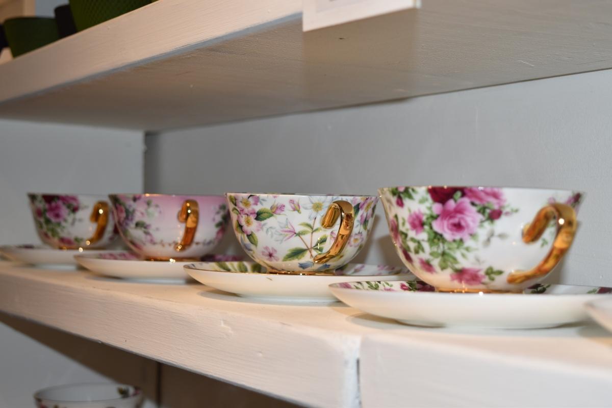 A photograph of four teacups and saucers on a shelf.