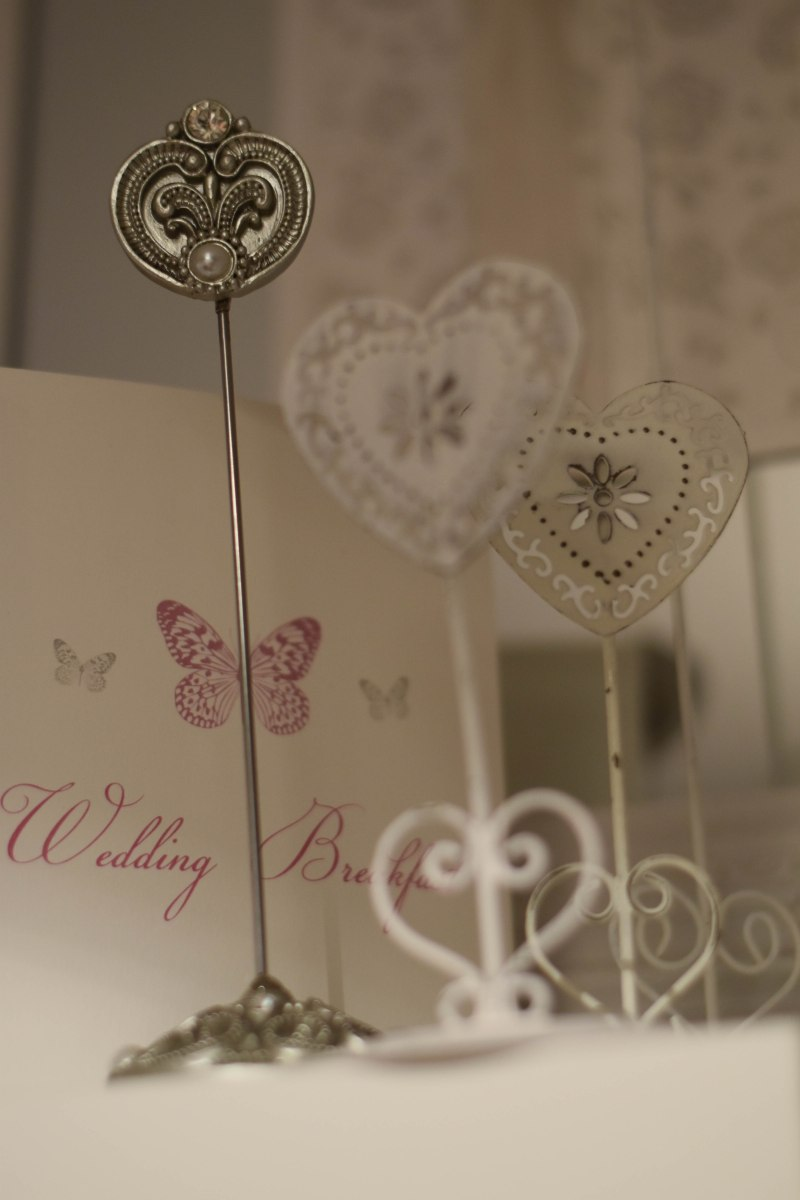 A photograph of three heart-shaped photo or card holders in front of a wedding menu card made by Julie