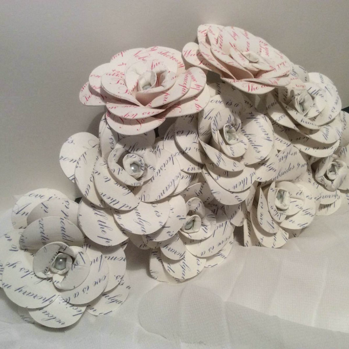 A photograph of around a dozen paper flowers in a bouquet made by Julie for a wedding