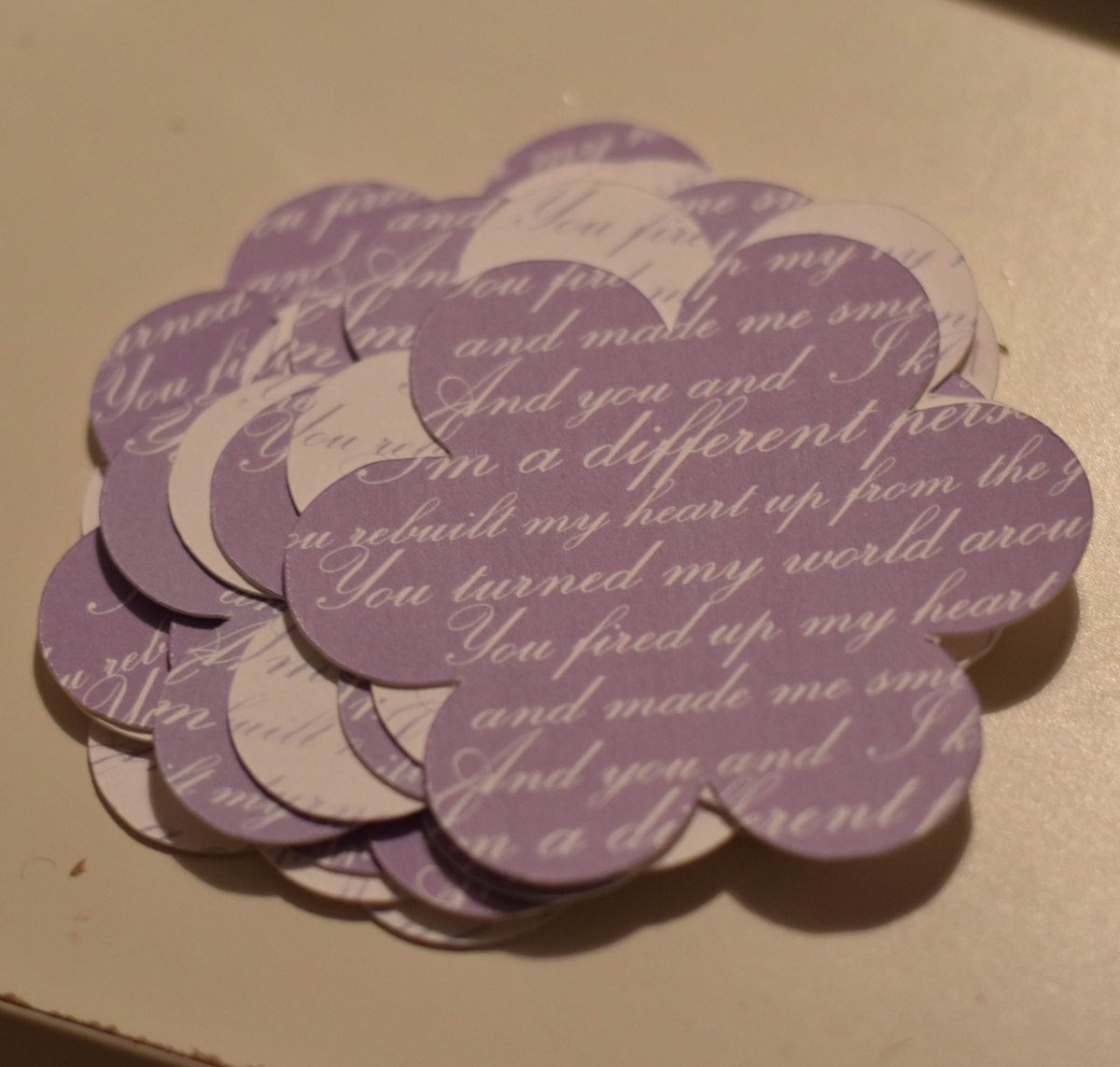 A photograph of a pile of the cut flower shapes with lyrics printed over them