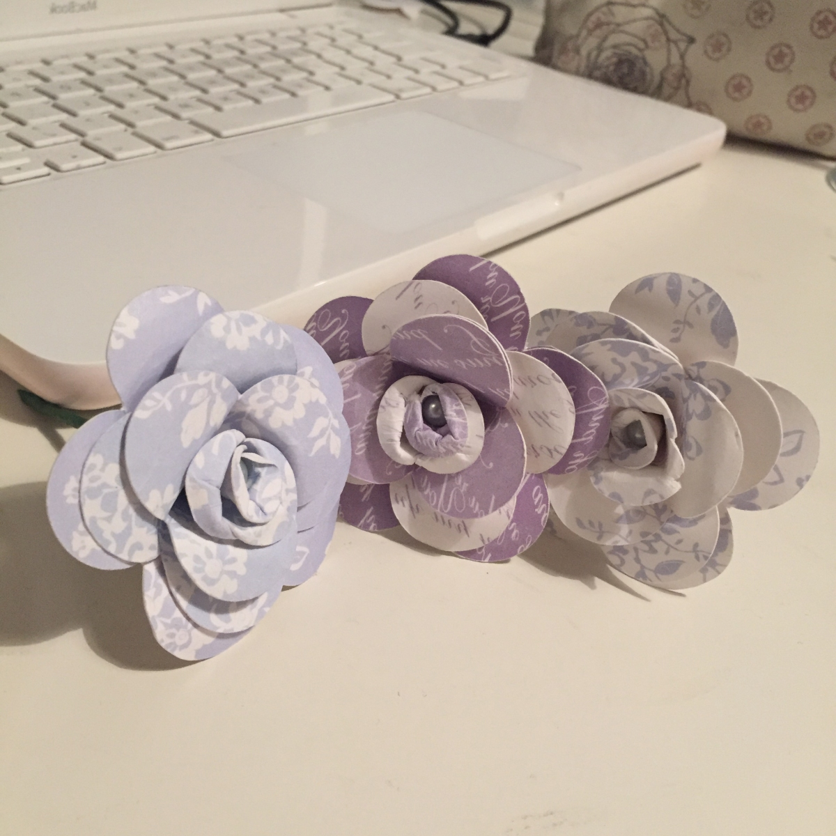 A photograph of three flowers in a row in front of the laptop