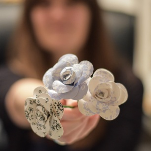 A photograph of Julie holding three flowers