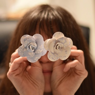A photograph of Julie holding two flowers in front of her like glasses