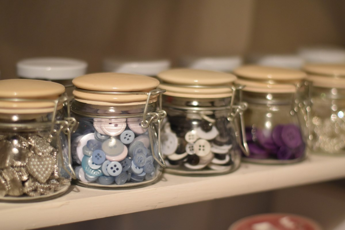 A photograph of lots of glass jars filled with buttons