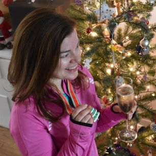 A photograph of Emma posing with her medal and holding a glass of prosecco