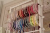 A photograph of spools of ribbons in all the colours of the rainbow
