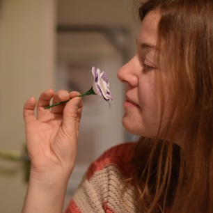 A photograph of Emma posing as if to smell the flower
