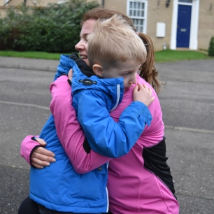A photograph of Emma's son, Ollie, giving Emma a big cuddle