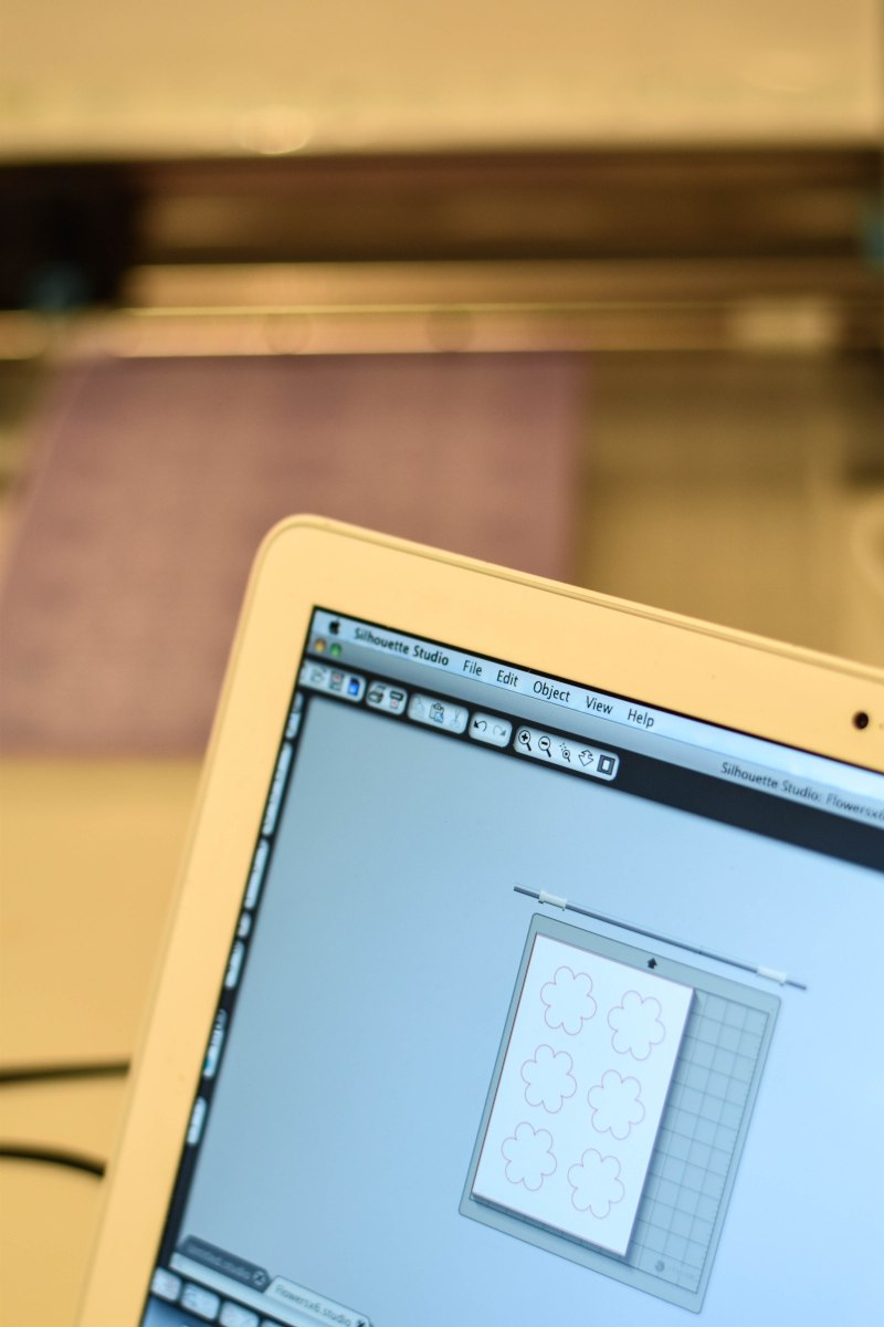 A photograph of the laptop screen showing the flower template ready to print