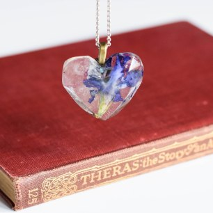 A photograph of the periwinkle pendant hanging over a red vintage book